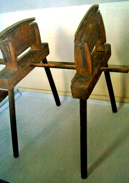 Harness and heddle maker: two parallel wooden pieces held together by a rod, a dowel would fit between the holes at the top, two slats would be in the slots at the top. Heddles are knitted around the slats and dowel, forming the heddle eye.