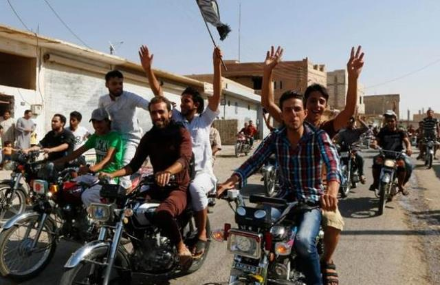 Residents of Tabqa city tour the streets on motorcycles, carrying flags in celebration after Tabqa air base fell to Islamic State militants, in nearby Raqqa city August 24, 2014. REUTERS/Stringer
