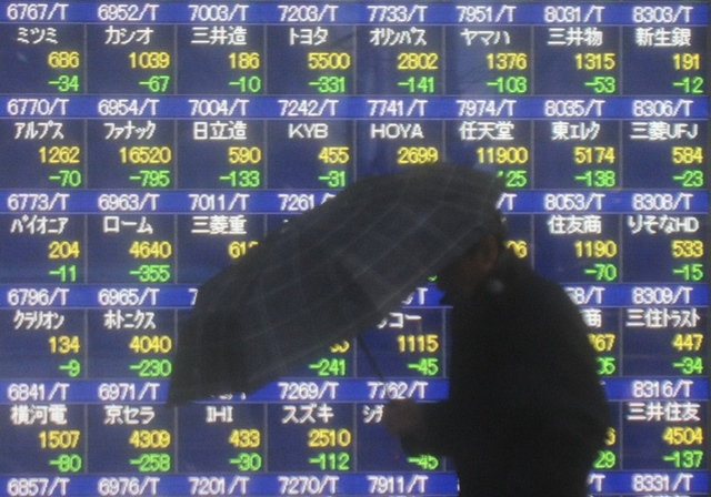 A man walks past an electronic board showing the stock index in Tokyo, Japan, Feb. 4, 2014. Tokyo stocks tumbled on Tuesday, with the Nikkei index ending 4.18 percent lower, hitting the lowest closing level since last October. The 225-issue Nikkei Stock Average dived 610.66 points, from Monday at 14,008.47, its lowest finish since Oct. 8. (Xinhua/Stringer)