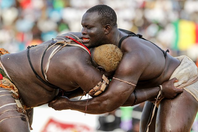 "Wrestlers compete in the Senegalese traditional wrestling match ""Le Choc"" at Demba Diop Stadium, Dakar, capital of Senegal, April 5, 2015. Thousands of audience have watched the biggest match here on Sunday at the beginning of the wrestling season with the most famous wrestlers Balla Gaye 2 and Eumeu Sene competing. Eumeu Sene won the match at last. (Xinhua/Li Jing)"