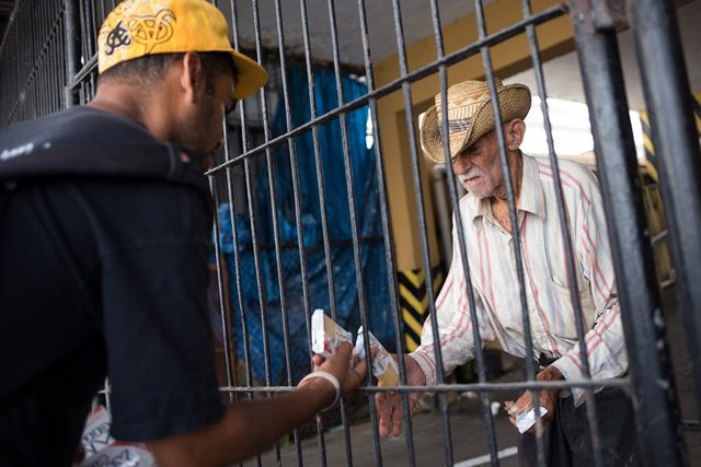 Image taken on April 4, 2015 shows Felix Cepeda (L), son of farmers of La Vega Province who migrated searching for better economic conditions, delivering cookies to a poor person who sleeps in a parking in the Colonial Zone, in Santo Domingo, Dominican Republic. Felix Cepeda has become a social worker for 15 years in Dominican Republic. During the Holy Week, Felix Cepeda and his friend David Janicki attended religious celebrations and visited people in povery, with whom they share water, cookies and talks, bringing them emotional support. (Xinhua/Fran Afonso) (rtg)