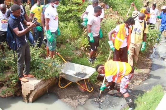 Gyan and Adebayor desilting a gutter in Kumasi