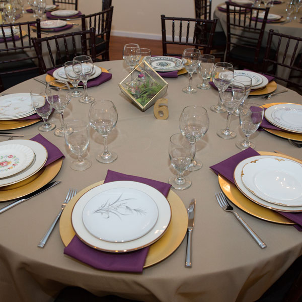 Table set up on a round table with vintage mixed china and gold chargers and glassware.