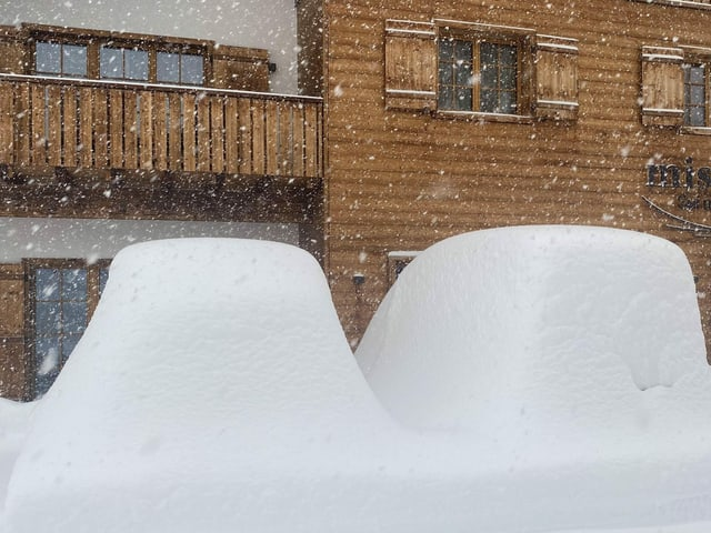 Snow-covered cars in front of a chalet.