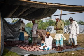 Residents of the Dotma Relief Camp offer their afternoon prayers at a makeshift mosque inside the camp.