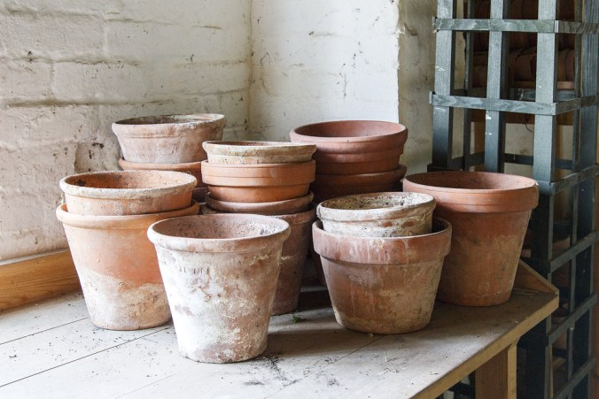 stacks of clay pots on an outdoor table