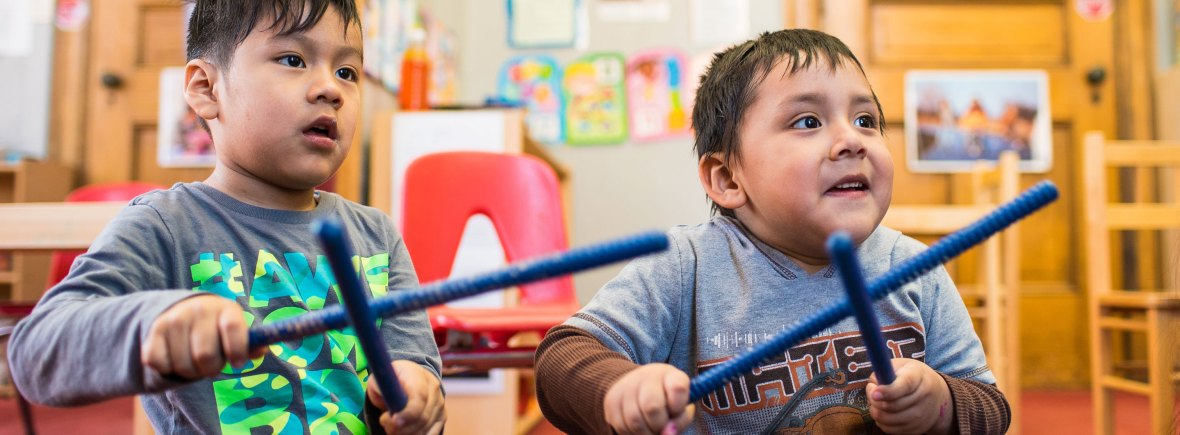 Two young boys sitting and playing blue rhythm sticks