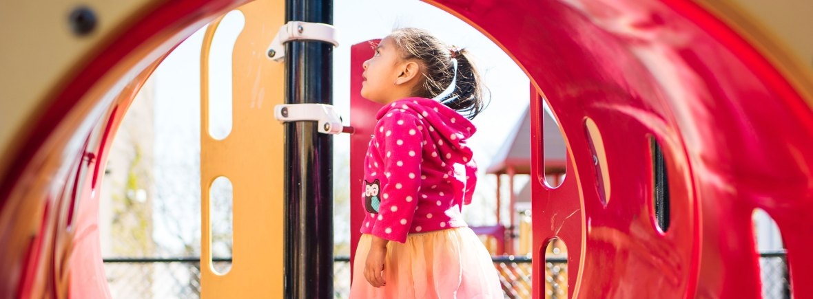 Looking through a playground crawl tube at young girl in a pink dress