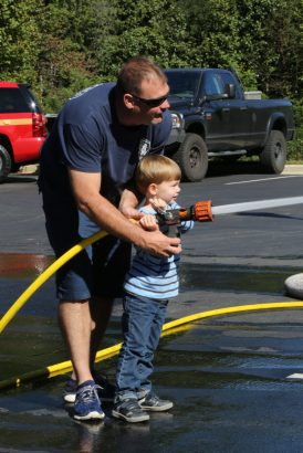 Sandy Spring Volunteer Fire Department Board member John Lindner shows 4 year old Henry Ketchum of Silver Spring how to use a fire hose during the Sandy Spring Volunteer Fire Department Open House held at Station 4 on Brooke Road last Sunday afternoon (10/1/17).