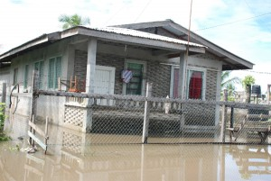 Swamped! This flat house at Bachelor's Adventure, East Coast Demerara was completely surrounded by water yesterday, which undoubtedly would have gone inside as well. (Photo by Jules Gibson)
