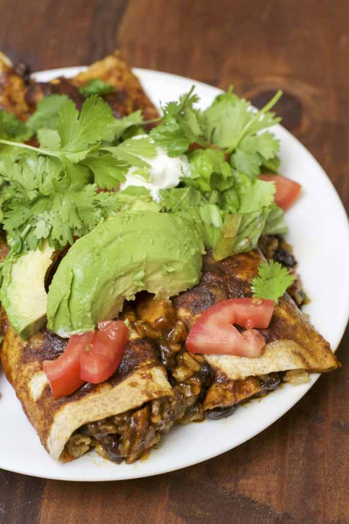 Roasted sweet potato black bean enchiladas covered in a homemade spicy enchilada sauce and stuffed with a flavorful vegetarian filling. We love these enchiladas any night of the week, especially because they're ready in less than one hour!