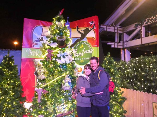 A couple smiling in front of a Christmas tree in the Tree Trail at Disney Springs.
