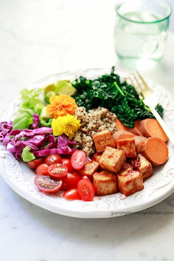 Low-carb vegan BBQ tofu with red cabbage, tomatoes, sweet potatoes, greens, flowers, and quinoa in a white bowl on a white background.