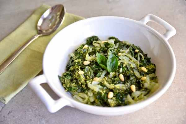 A white bowl containing low-carb vegan pesto shirataki noodles with basil and pine nuts and there is a spoon resting on a green napkin to the left.