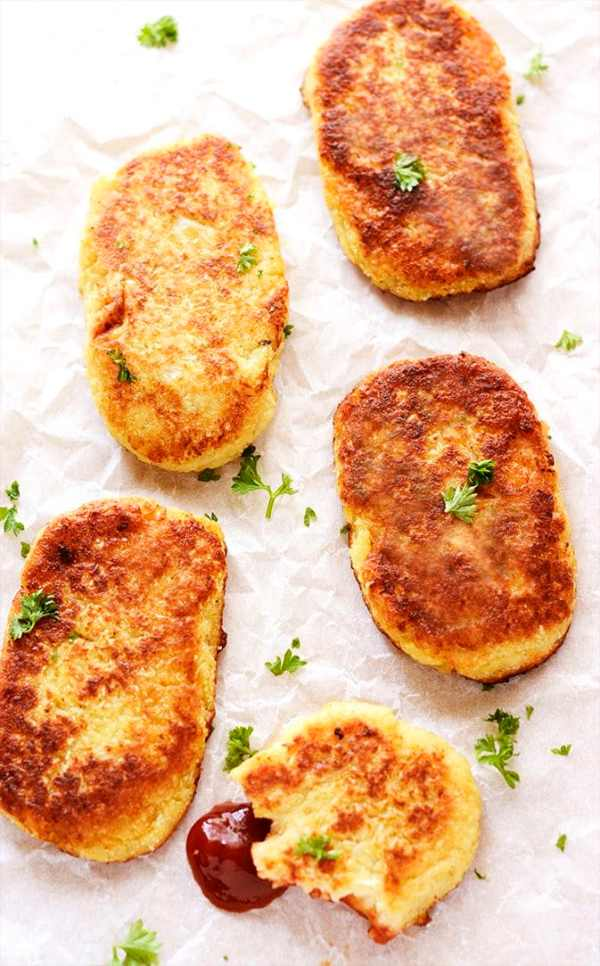 Low-carb vegan cauliflower hash browns resting on a textured white background.