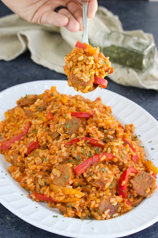 A hand holding a spoonful of vegan sausage and peppers with rice over a white platter on a textured background.