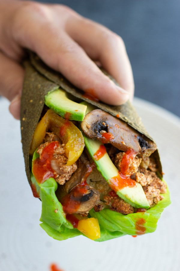 A hand holding a wrapped up roasted vegetable and tofu taco with hot sauce drizzled over it.