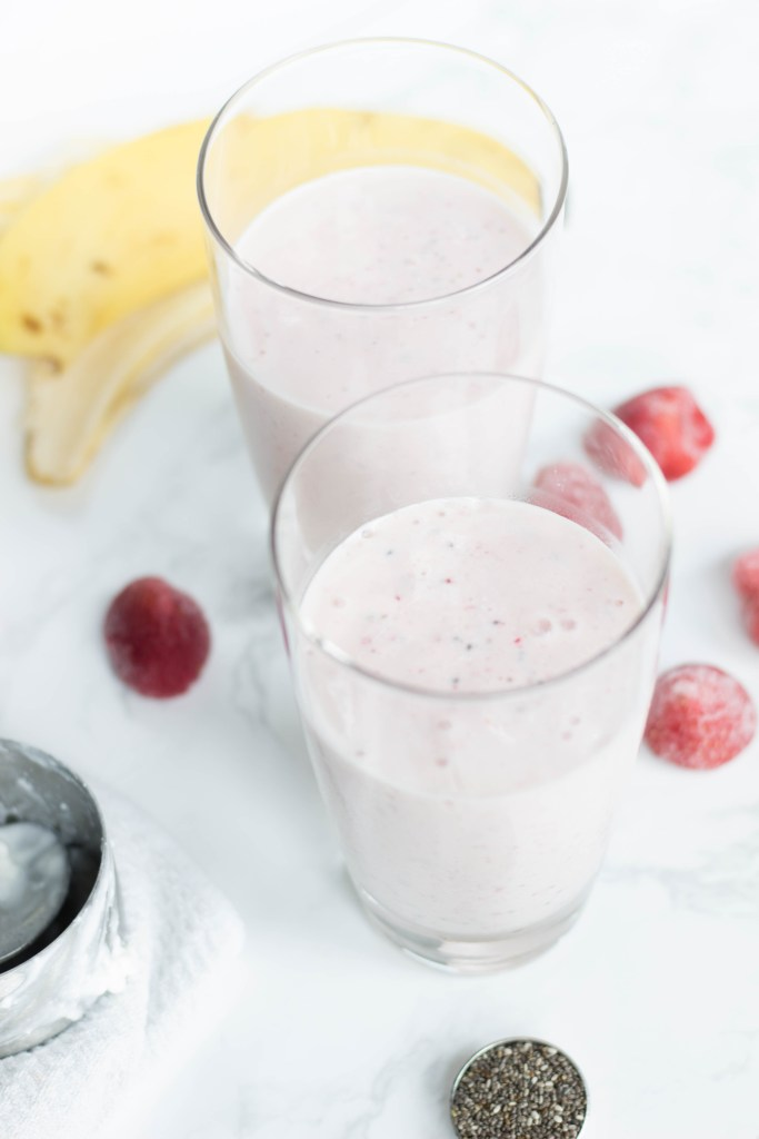 Strawberry banana smoothie filled in two glass cups with frozen strawberries and chia seeds