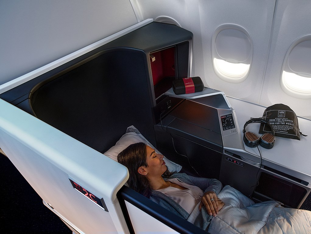 blanket in business class seat bed in airplane cabin