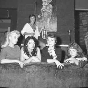 A group of beatnik girls pose on a couch.