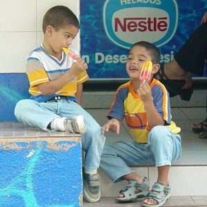 Two young boys enjoy Popsicles on a hot summer day.