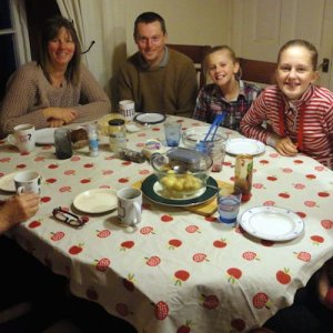 A family sits around a set dinner table, all smiles in a display of proper table etiquette.