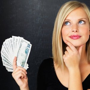A young woman holds a fanned-out wad of cash, contemplating with a smirk and her chin in her opposite hand.