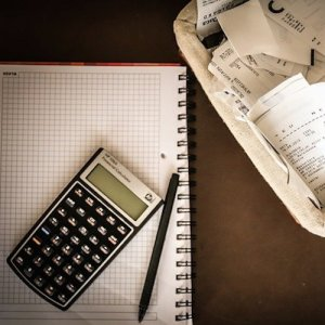 Financial planing materials laid out on a desk: a calculator, pen, graphing paper, and a basket of reciepts are all present.