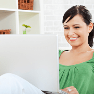 A woman smiles as she uses her laptop computer in a minimally decorated room.