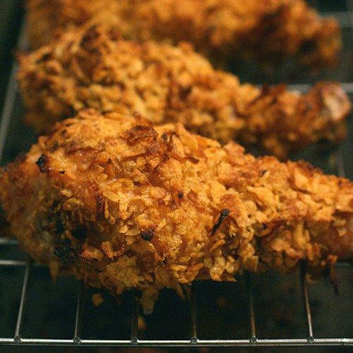 Crispy-baked chicken drumsticks on an oven rack.