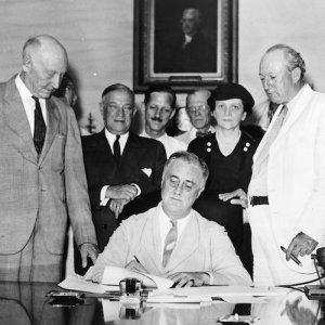 U.S. President Franklin Delano Roosevelt signs the Social Security Act into law.