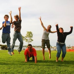 Parents and their adult children jumping in the air for a family photo on a rolling, green lawn..