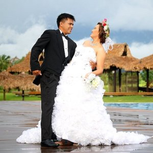 A couple smiles at each other during their wedding photo shoot.