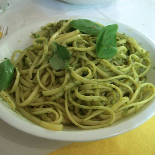 A large bowl of linguini noodles covered in pesto sauce and topped with basil leaves.