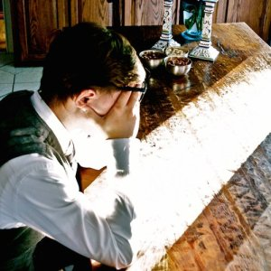A young man sits slumped at a desk, blocking his eyes from incoming sunlight.