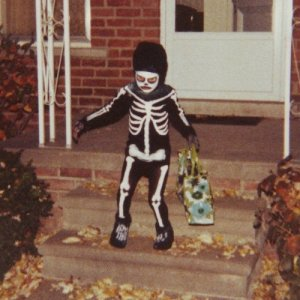 A child trick-or-treats in a homemade skeleton outfit.