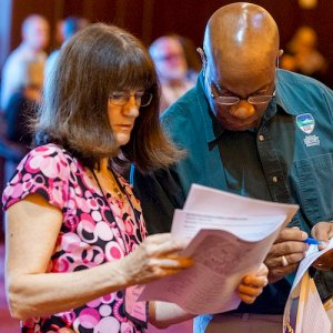 A man and woman lean together, trying to make sense of confusing paperwork.