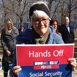 """A woman at a rally holds a sign reading, """"Hands Off my Social Security."""""""