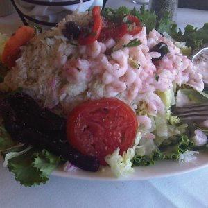 A bed of garden greens topped with tons of baby shrimp and crab meat.