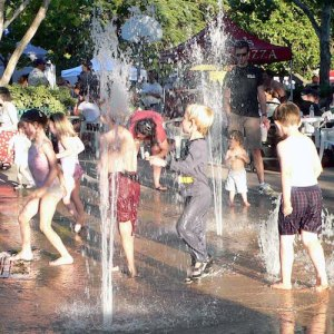 Children playing in an urban fountain on a hot summer day.