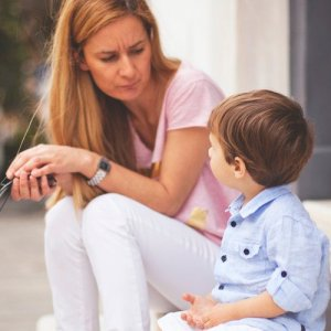 A young boy looks up to his mother as she explains a concept to him.