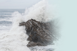 A massive wave crashes over a large rock formation at the ocean's edge.