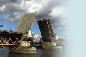The Burnside Drawbridge in Portland, OR lifts up into it's open position across the Willamette River on a partly cloudy day.