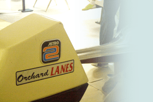 """A closeup of a ball return at a """"Orchard Lanes"""" bowling alley."""