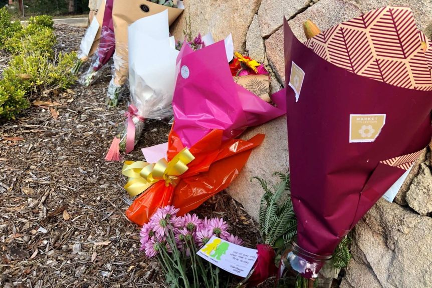 Floral tributes left on the driveway of the house where the bodies of Loris and Franco Puglia were found.