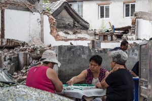 Women play mahjong amongst the rubble