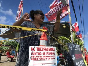 DENNIS ODA / DODA@STARADVERTISER.COM                                 Fisiipeau Drummonde was among the protesters against wind-energy turbines who remained outside the Kahuku Agricultural Park this morning