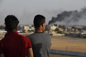 ASSOCIATED PRESS People standing on a rooftop in Akcakale, Sanliurfa province, southeastern Turkey, at the border with Syria, watch as in the background smoke billows from fires caused by Turkish bombardment in Tal Abyad, Syria, today. Turkey's official Anadolu news agency says Turkey-backed Syrian forces have advanced into the center of a Syrian border town, Tal Abyad, on the fifth day of the Turkey's military offensive against Kurdish fighters in Syria.