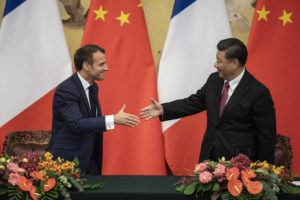 NICOLAS ASFOURI/POOL PHOTO VIA ASSOCIATED PRESS                                 French President Emmanuel Macron, left, shook hands with Chinese President Xi Jinping following a signing ceremony at the Great Hall of the People in Beijing, Wednesday.