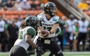 ASSOCIATED PRESS                                 Hawaii quarterback Cole McDonald handed off the football to running back Miles Reed during the first half of the Hawaii Bowl against BYU, Tuesday. The largest TV audience to watch a University of Hawaii football game in 11 years saw the Rainbow Warriors rally past Brigham Young in the SoFi Hawaii Bowl Tuesday.